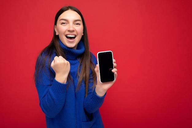 Gelukkige jonge vrouw, gekleed in casual blauwe trui geïsoleerd op rode achtergrond met