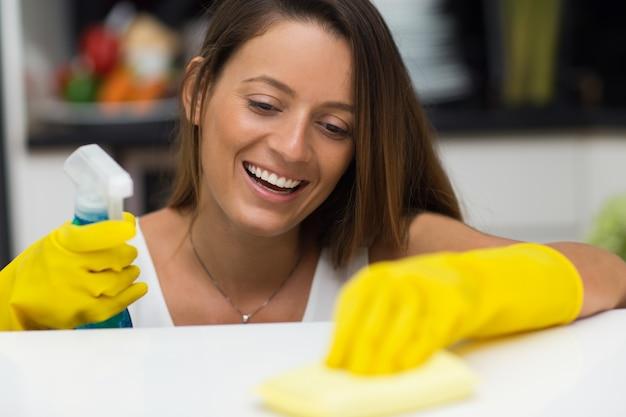Gelukkige jonge vrouw genieten van het schoonmaken