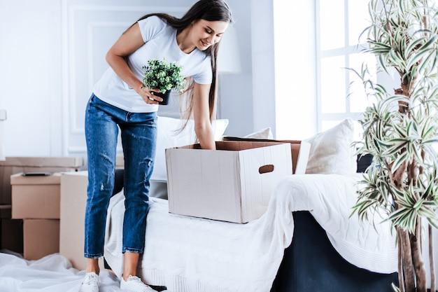 Gelukkige jonge vrouw haalt dingen uit kartonnen dozen. verhuizen naar een nieuw appartement