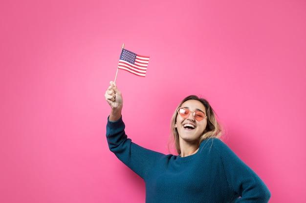 Gelukkige jonge vrouw hartvormige bril met amerikaanse vlag tegen een studio roze achtergrond