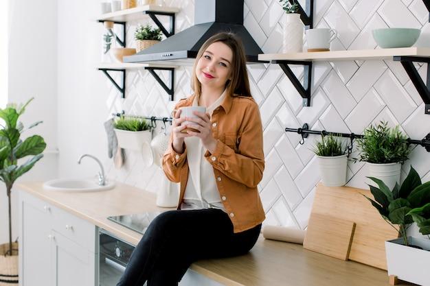 Gelukkige jonge vrouw het drinken koffie terwijl thuis het zitten bij de keuken in de ochtend