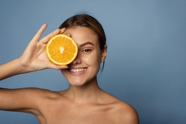 Gelukkige jonge vrouw houdt een halve sinaasappel op haar gezicht op een blauwe achtergrond