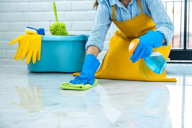 Gelukkige jonge vrouw in blauw rubber die doek gebruiken terwijl thuis het schoonmaken op vloer