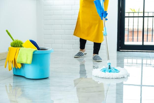 Gelukkige jonge vrouw in blauw rubber die zwabber gebruiken terwijl thuis het schoonmaken op vloer