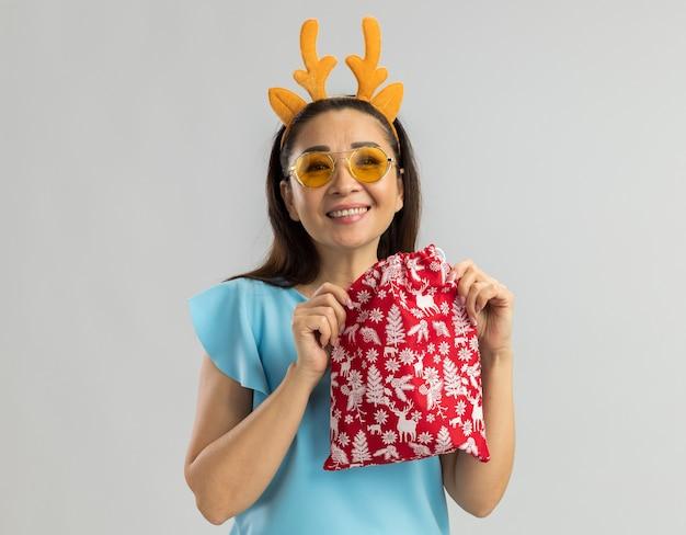 Gelukkige jonge vrouw in blauwe bovenkant die grappige rand met hertenhoornen en gele glazen draagt die kerstmiscadeau houden die met grote glimlach op gezicht kijken