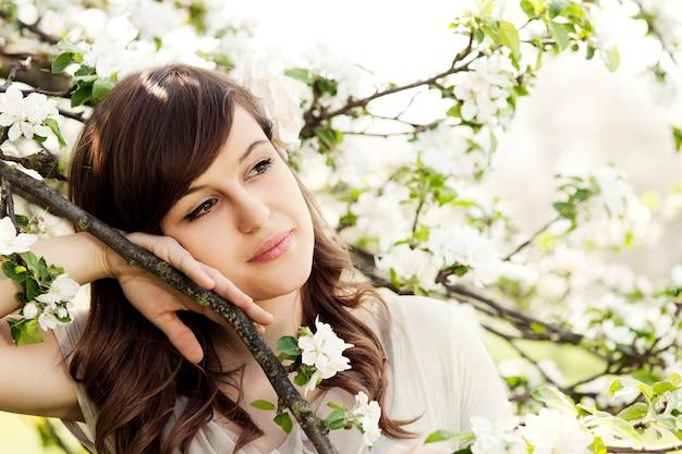 Gelukkige jonge vrouw in de boomgaard