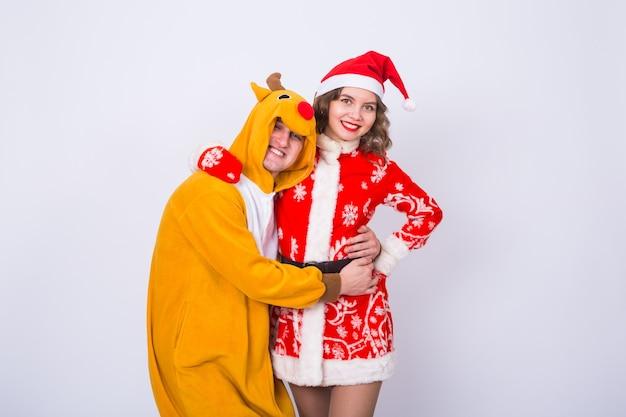 Gelukkige jonge vrouw in de hoed van de kerstman en man in carnaval-kostuum van herten. pret-, vakantie-, grap- en kerstconcept.