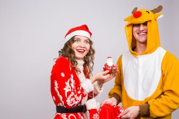 Gelukkige jonge vrouw in de hoed van de kerstman en man in carnaval-kostuum van herten.