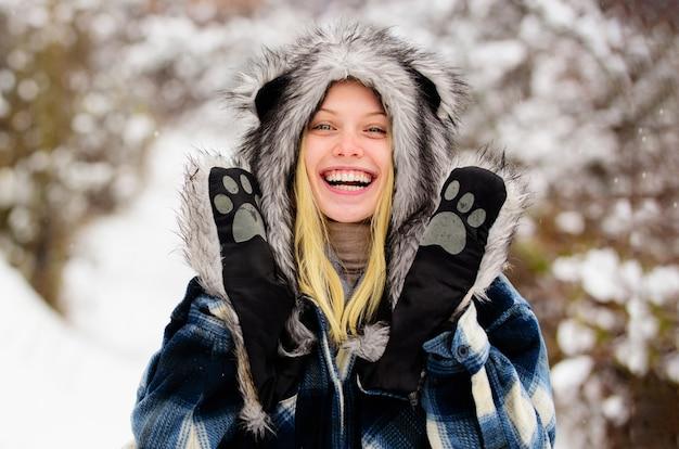 Gelukkige jonge vrouw in de winter. glimlachend meisje in sneeuwpark. mooie vrouw in warme jas en bontmuts.
