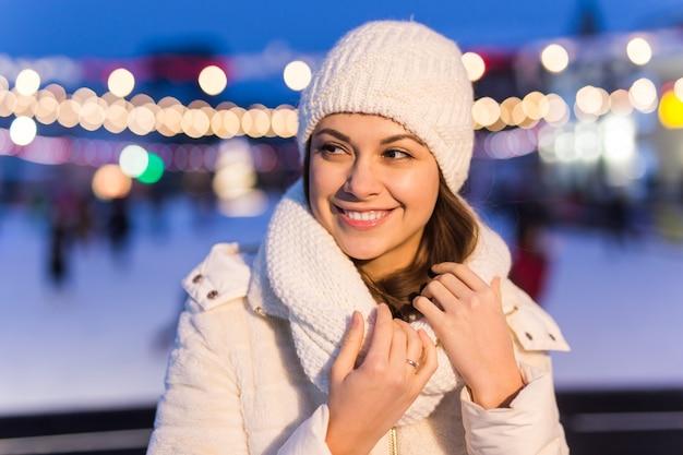 Gelukkige jonge vrouw in de winter in de buurt van de ijsbaan. kerst- en winterconcept.