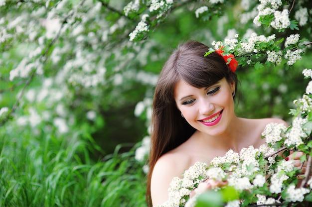 Gelukkige jonge vrouw in een de lentepark dat de bloemen ruikt