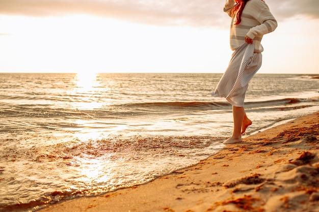 Gelukkige jonge vrouw in een kleding die alleen op leeg zandstrand bij zonsondergangzeekust lopen en water met haar voeten raken. freedoom, vakantie