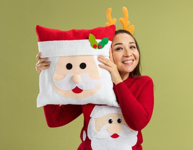 Gelukkige jonge vrouw in een rode kersttrui met een grappige rand met hertenhoorns die een kerstkussen vasthoudt en vrolijk lacht over de groene muur