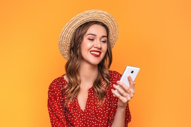 Gelukkige jonge vrouw in een rode kleding die van de strohoed haar cel bekijken en glimlachen geïsoleerd op een oranje muur. meisje leest een bericht online aankopen bestelt goederen op het internet