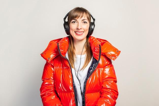Gelukkige jonge vrouw in een rood jasje en hoofdtelefoons die aan geïsoleerde muziek luisteren