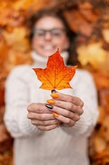 Gelukkige jonge vrouw in een stijlvolle gebreide witte trui toont de camera een prachtig oranje esdoornblad. blij meisje ligt in de herfst kleurrijk geelgoud gebladerte. close-up van een esdoornblad in vrouwelijke handen.