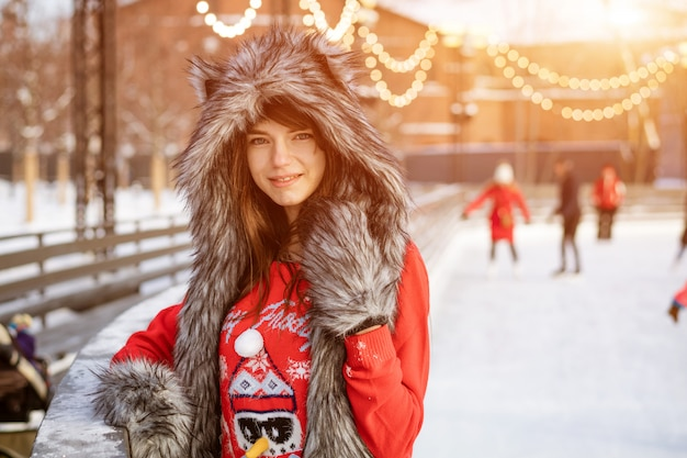 Gelukkige jonge vrouw in een wolfshoed in de winter op ijsbaan het stellen in een rode sweater