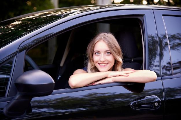Gelukkige jonge vrouw in een zwarte auto.