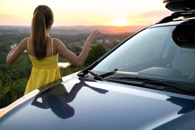Gelukkige jonge vrouw in gele jurk die in de buurt van haar voertuig staat en kijkt naar de zonsondergang van de zomerse natuur. reizen en vakantie concept.