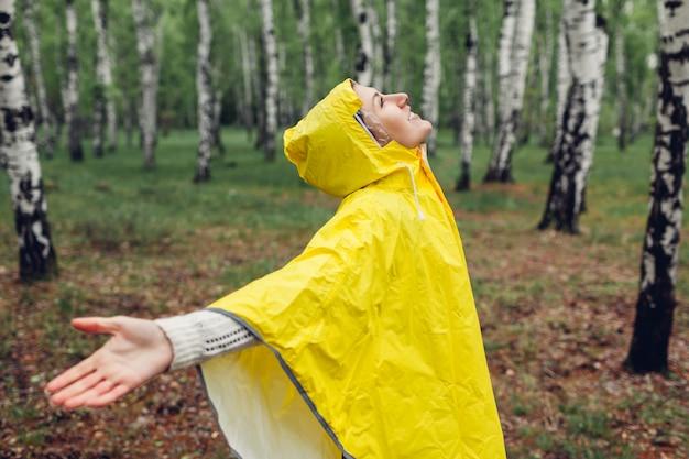 Gelukkige jonge vrouw in gele regenjas die in de lentebos lopen onder regen en pret hebben die wapens opheffen