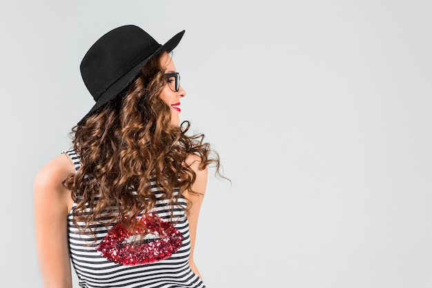 Gelukkige jonge vrouw in glazen en hoed op grijze studiomuur
