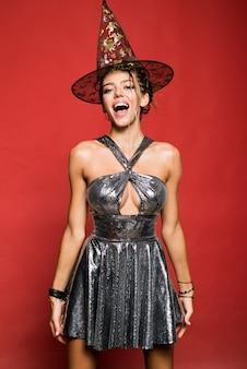Gelukkige jonge vrouw in het kostuum van heksenhalloween met hoed die en zich over rode muur bevinden glimlachen.
