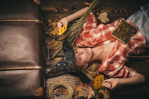 Gelukkige jonge vrouw in het kostuum van heksenhalloween op partij over geïsoleerde muur. de vrij jonge blonde vrouw kleedde zich als fee met pompoen.