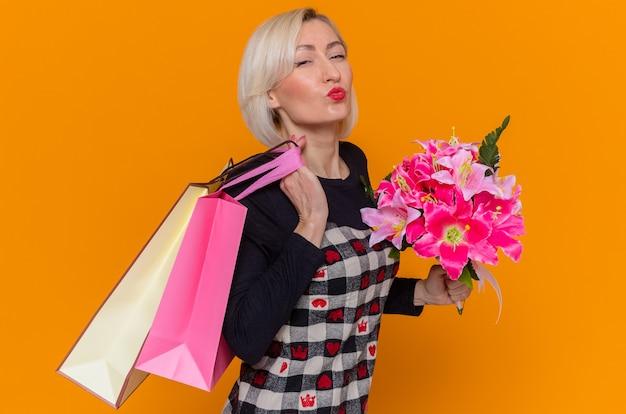 Gelukkige jonge vrouw in het mooie boeket van de kledingsholding bloemen