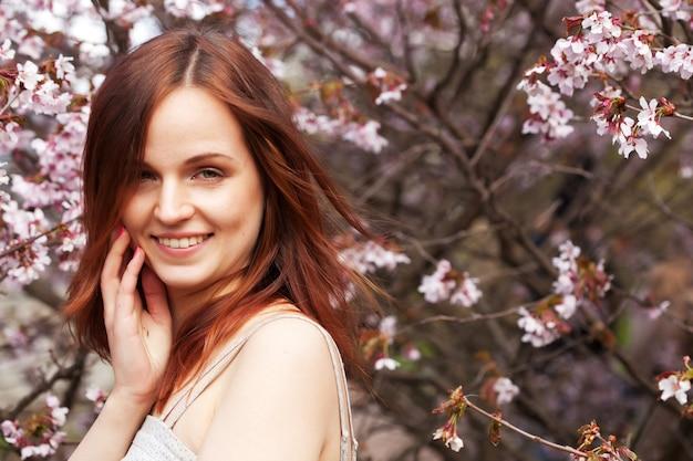 Gelukkige jonge vrouw in het portret van de de tuinlevensstijl van de lentebloemen. sakura tuin.