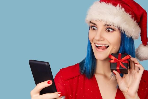 Gelukkige jonge vrouw in kerstmuts met geschenkdoos en smartphone over blauwe achtergrond