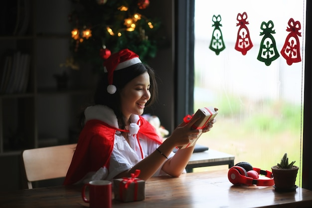 Gelukkige jonge vrouw in kerstmuts met kerstcadeau.