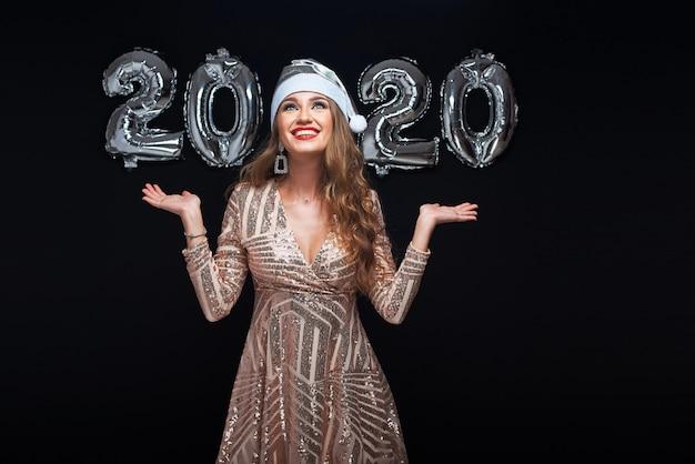 Gelukkige jonge vrouw in kerstmuts met metalen 2020-ballonnen op zwart.