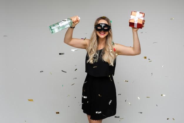 Gelukkige jonge vrouw in korte zwarte jurk en masker viert nieuwjaar met een fles en een cadeautje