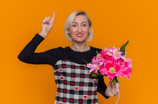 Gelukkige jonge vrouw in mooie jurk met boeket bloemen kijken naar voorzijde met wijsvinger glimlachend vrolijk vieren internationale vrouwendag staande over oranje muur