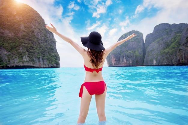 Gelukkige jonge vrouw in rode bikini op het strand.