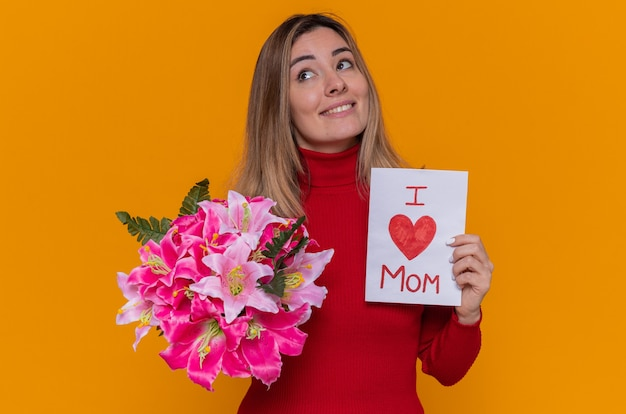 Gelukkige jonge vrouw in rode coltrui met wenskaart en boeket bloemen glimlachend vrolijk vieren moederdag