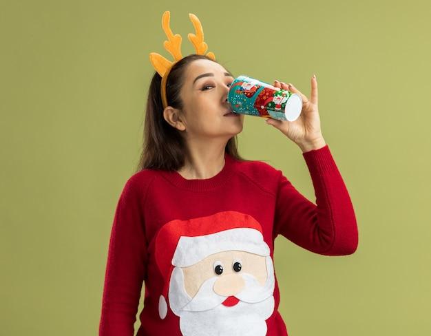 Gelukkige jonge vrouw in rode kerstmissweater die grappige rand met hertenhoorns draagt die uit kleurrijke document glb drinken