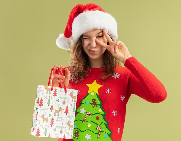 Gelukkige jonge vrouw in rode kersttrui en kerstmuts met papieren zak met kerstcadeaus knipogend met v-teken dat over groene muur staat