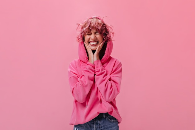 Gelukkige jonge vrouw in roze hoodie glimlacht breed op geïsoleerd