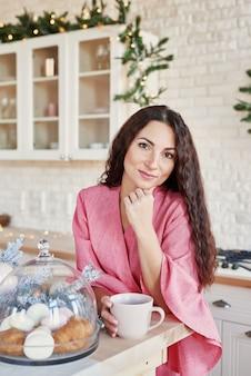 Gelukkige jonge vrouw in roze kleding met kop in kerstmis verfraaide keuken. mooie brunette met kop cacao in keuken met kerstdecor. licht wit keukenbinnenland voor kerstmis. vrouw thuis