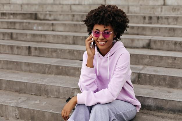 Gelukkige jonge vrouw in roze zonnebril praat buiten aan de telefoon