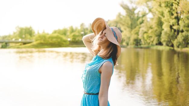 Gelukkige jonge vrouw in strohoed in zonnige tuin