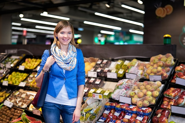 Gelukkige jonge vrouw in supermarkt