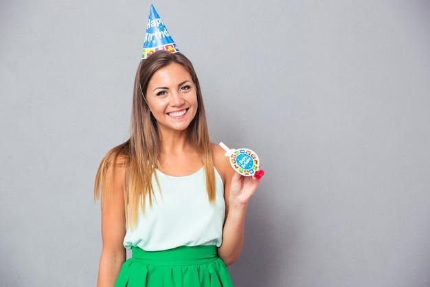 Gelukkige jonge vrouw in verjaardagshoed en fluitje