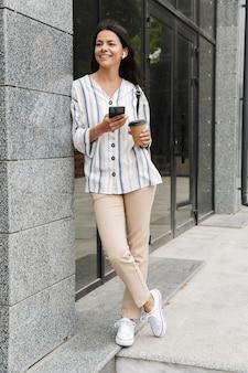 Gelukkige jonge vrouw in vrijetijdskleding die afhaalkoffie drinkt en mobiele telefoon vasthoudt terwijl ze boven het gebouw staat