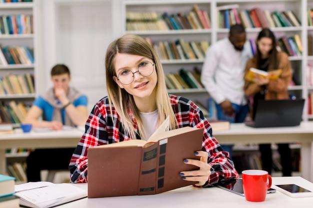 Gelukkige jonge vrouw in vrijetijdskleding en oogglazen die in de bibliotheek met boek zitten, die informatie zoeken voor haar studies.