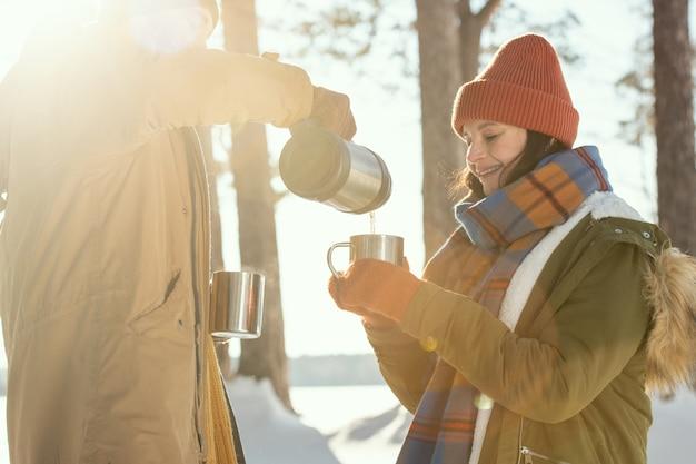 Gelukkige jonge vrouw in warme winterkleding met metalen mok terwijl haar man hete thee voor de camera giet tegen pijnbomen
