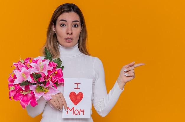 Gelukkige jonge vrouw in witte coltrui met wenskaart en boeket bloemen