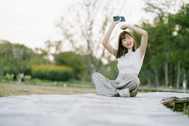 Gelukkige jonge vrouw in witte kleren met oortelefoons die op houten gang in het park zitten en pret hebben terwijl het gebruiken van mobiele telefoon die aan muziek luisteren met haar ogen open kijkend vanaf de camera