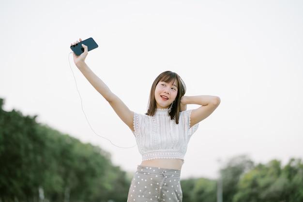 Gelukkige jonge vrouw in witte kleren met oortelefoons die pret hebben terwijl het gebruiken van mobiele telefoon die aan muziek luisteren met haar open ogen kijkend vanaf de camera in het park